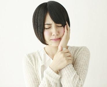 顎関節症に苦しむ若い女性