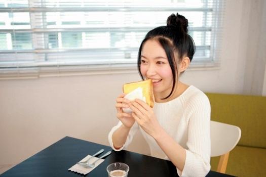マーガリンを塗ったトーストを食べる若い女性