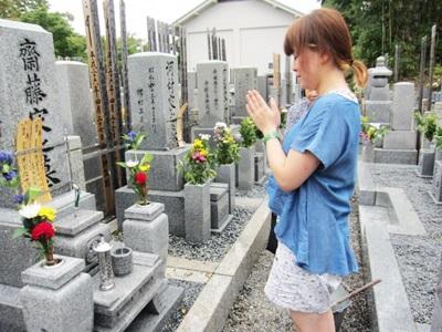 お彼岸のお墓参りで合掌する女性