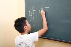 黒板に計算を書く男の子