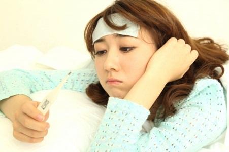 熱が出て体温を測る女性