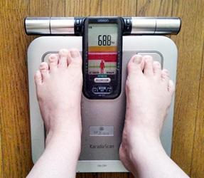 太りすぎで体重測定する人