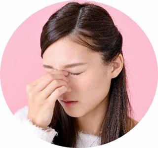 目の疲労で目頭を押さえる女性