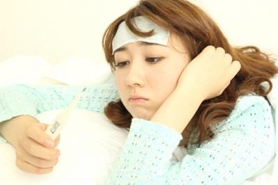 風邪で熱を測る女性