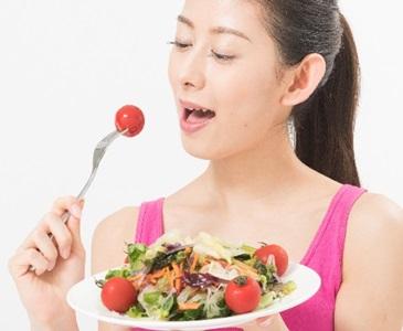 野菜サラダを食べる女性の画像