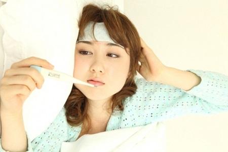 インフルエンザで熱を測る若い女性