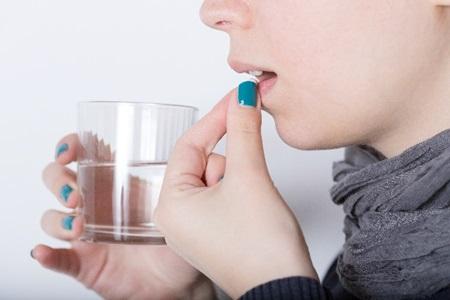 ビタミン剤を飲む女性