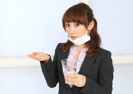 咳が止まらないので咳止めを飲む女性