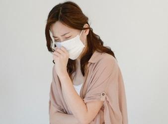 咳が止まらないマスクの女性