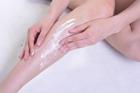 日焼け止めクリームを足に塗る女性