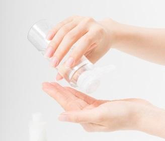 日焼け後に顔のアフターケアで化粧水をつける女性