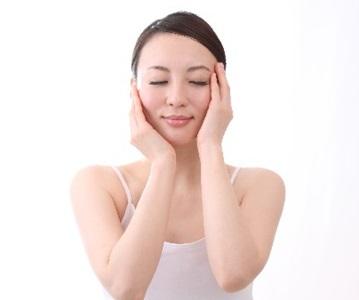 顔の日焼け対策をする女性のイメージ画像
