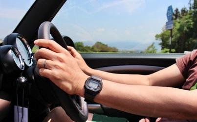 日光にさらされる運転中の両手の画像