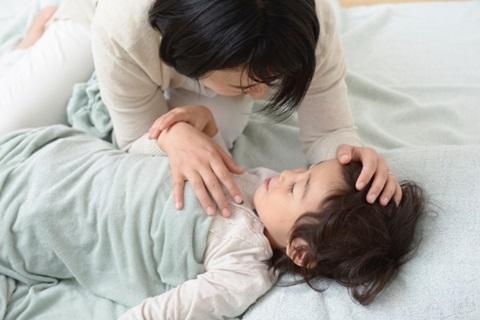 子供が眠るのを見守る母親