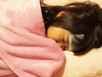 熱を出して毛布に包まる子供